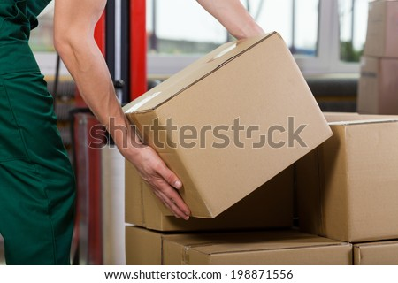 Hands of warehouse worker lifting box, horizontal - stock photo