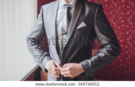 Hands of wedding groom getting ready in suit - stock photo