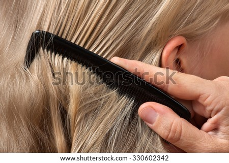 hands of woman combing hair her little daughter