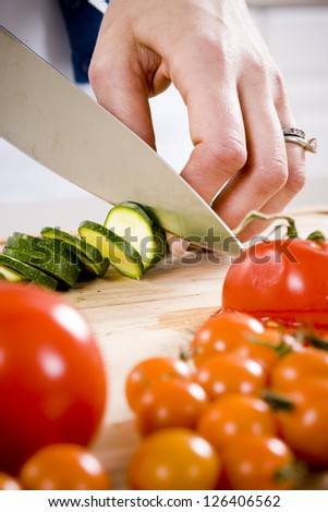 Hands of woman cutting vegetables