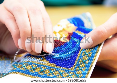 Hands of woman / female / girl bead embroidery ornament towel on wooden background