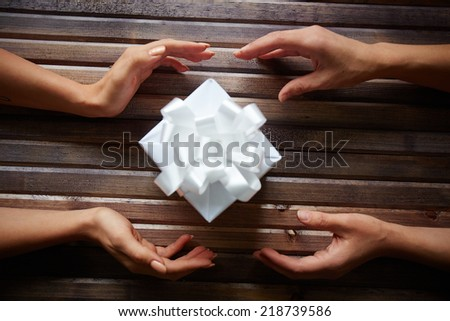 Hands of woman giving box with Christmas present to her friend on wooden background - stock photo