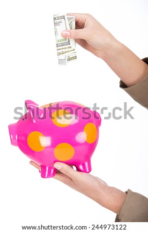 Hands of woman is putting money on a piggy bank, isolated on a white background. - stock photo