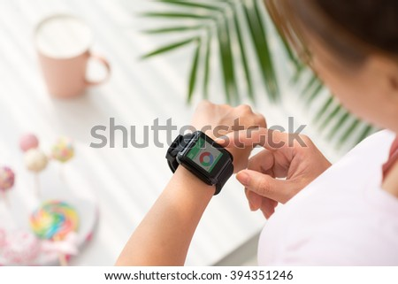 Hands of woman using application on her smart watch - stock photo