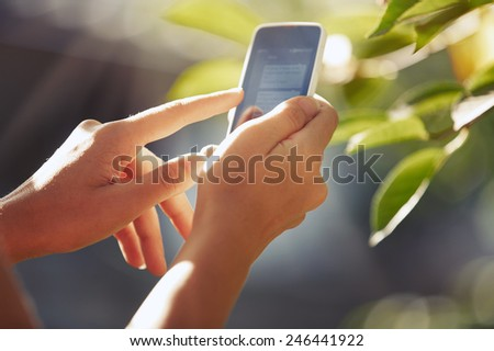 Hands of woman with smartphone in the garden