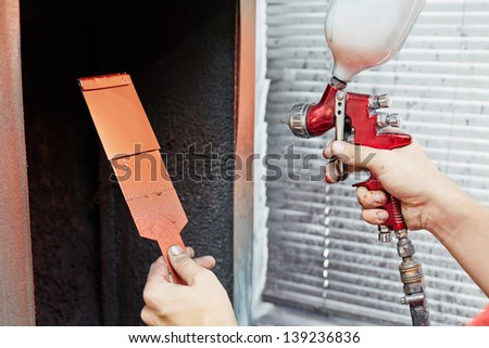 Hands of worker, who tries color for car painting, piece of metal in one hand and air-paint gun in another - stock photo