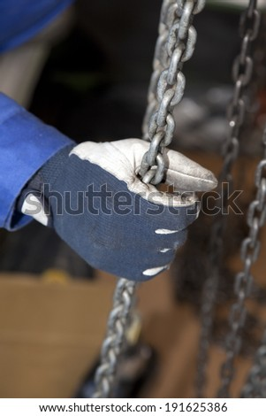 Hands of workers catching chain block