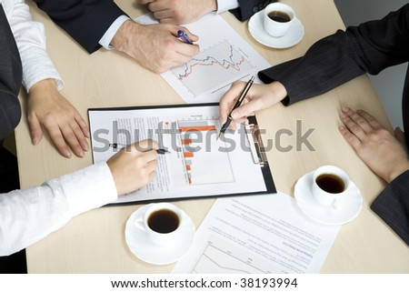 Hands of working businesspeople at meeting