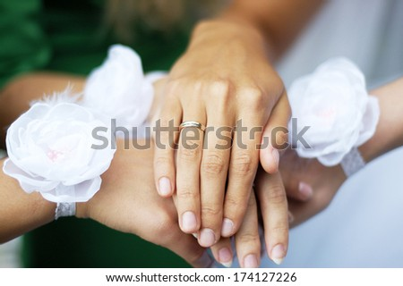 Hands of young bridesmaids with white flowers on the wrists and hand of bride with golden ring on the finger - stock photo