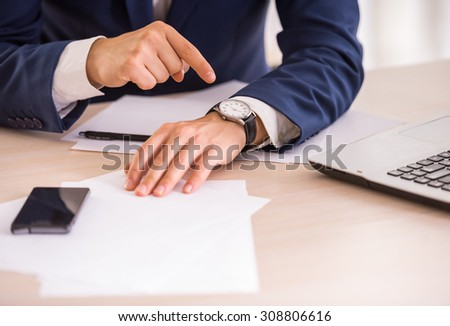 Hands of young businessman is pointing on the watch.