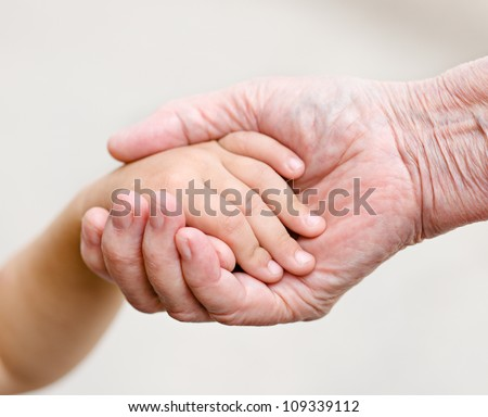 hands of young child and old senior - stock photo