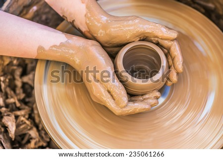 Hands of young potter, was produced on range of pot. - stock photo