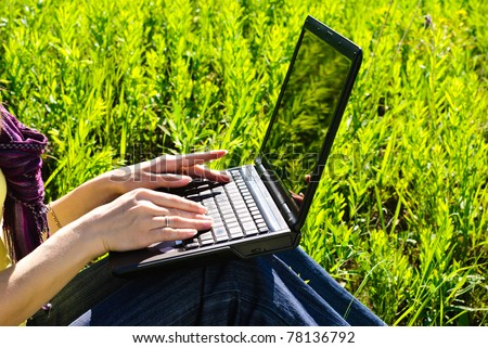 Hands of young woman on laptop outdoor. Sunny summer day. - stock photo