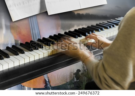 Hands of young woman playing the piano with other instrument and beautiful landscape in background - stock photo