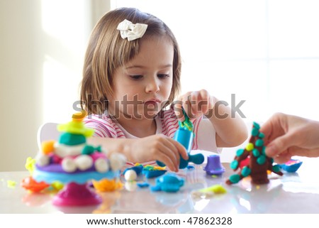 Hands of young woman show little girl how to use play dough - stock photo
