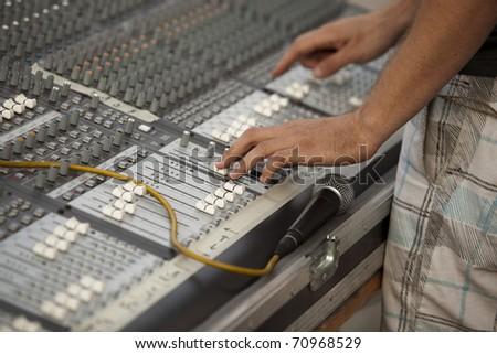 Hands on an audio mixer - stock photo
