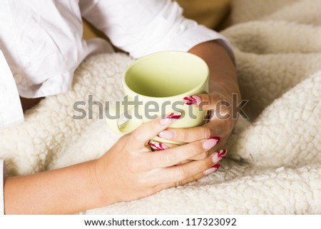 Hands on blanket with coffee