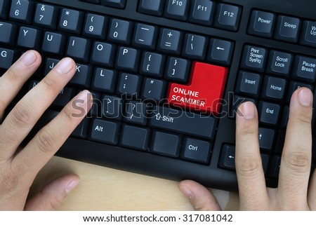 "Hands on computer keyboard with ""Online Scammer"" words at enter button. - stock photo"