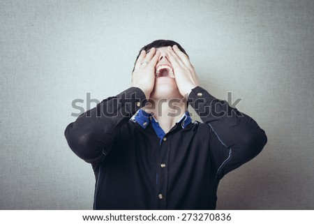 hands on face crying man on a gray background - stock photo