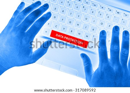 "Hands on laptop with ""DATA PROTECTION"" words on spacebar button on white background. - stock photo"