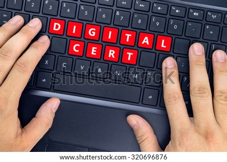 "Hands on laptop with ""DIGITAL CERT"" words on keyboard buttons. - stock photo"