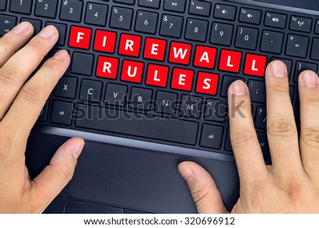 """Hands on laptop with """"FIREWALL RULES"""" words on keyboard buttons. - stock photo"""