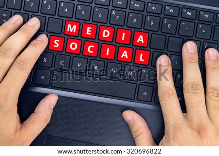 """Hands on laptop with """"MEDIA SOCIAL"""" words on keyboard buttons. - stock photo"""