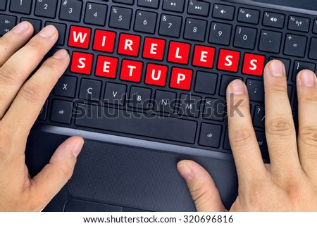 """Hands on laptop with """"WIRELESS SETUP"""" words on keyboard buttons. - stock photo"""