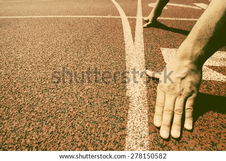 Hands on starting line - retro style photograph - stock photo