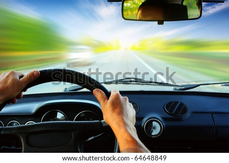 Hands on steering wheel of a car driving on an asphalt blurred road - stock photo