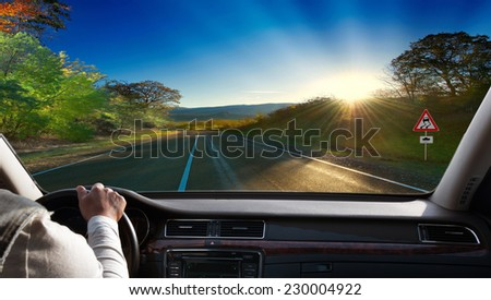 Hands on steering wheel of a car driving on an asphalt road  - stock photo