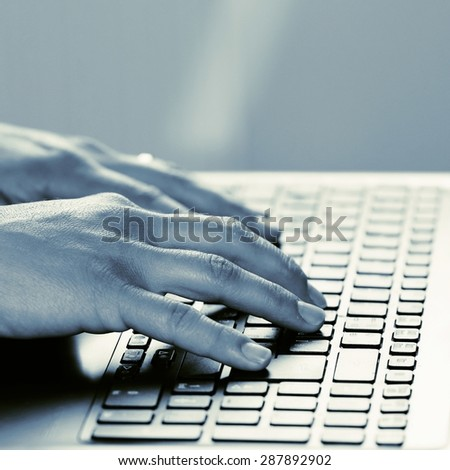 Hands on the keyboard. Office worker typing on the keyboard on the laptop.  - stock photo