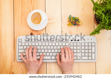 Hands on the keyboard over the wooden background - stock photo