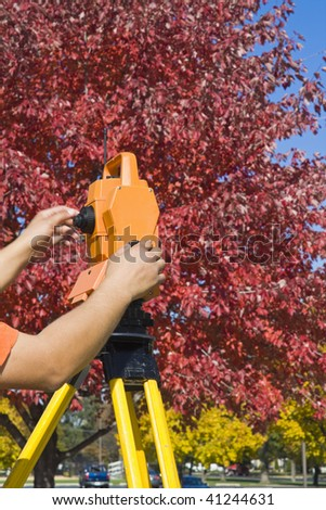 Hands on theodolite - land surveying during fall time. - stock photo