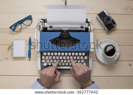 Hands on typewriter on the office desk - stock photo