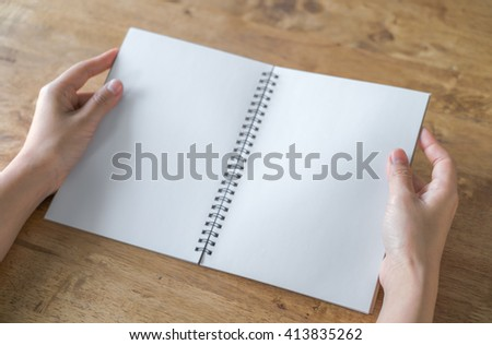 Hands open Blank catalog, magazines,book mock up on wood table - stock photo