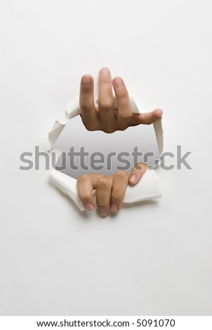 hands opening a hole in white cardboard - stock photo