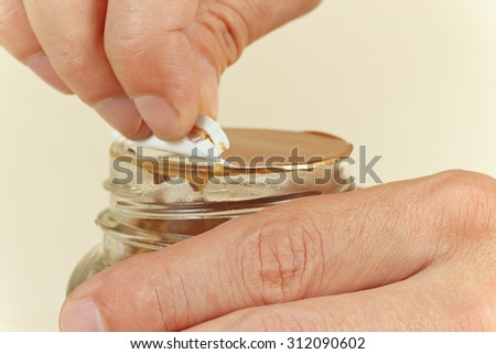 Hands opening a jar of instant coffee - stock photo