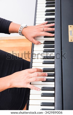 Hands os a classical musician woman playing on piano. - stock photo