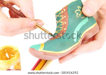Hands paints on and made ceramic saint patricks day boot and art materials, isolated on white - stock photo