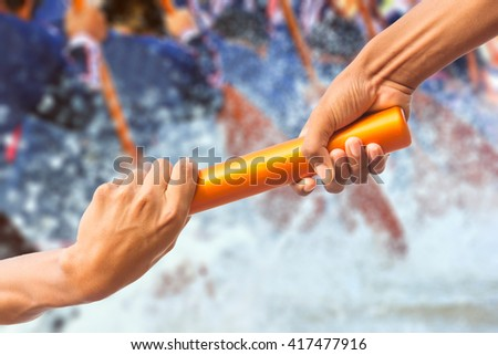 hands passing a relay baton on rowing team background - stock photo