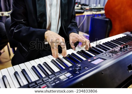 Hands pianist playing on digital piano in a jazz band closeup - stock photo
