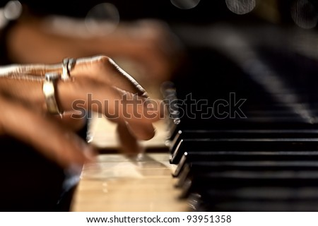Hands play on the piano - stock photo