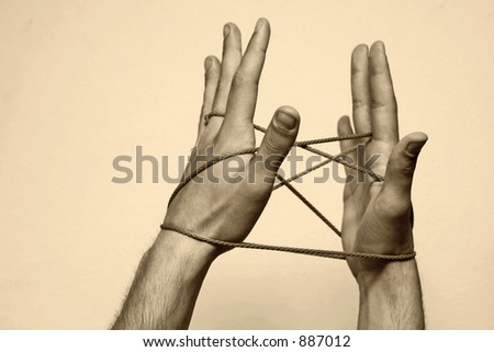 Hands playing with rope, symbolising connectivity, friendship, strong bonds. Sepia toning. - stock photo