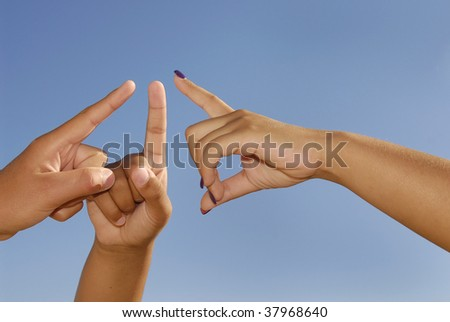 Hands pointing against a blue sky