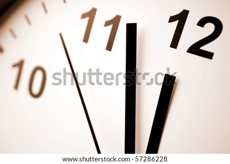 Hands pointing to midday on clock face - stock photo