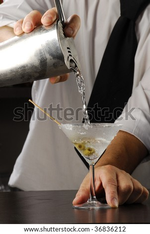 Hands, pouring a Martini cocktail. Bartender pouring liquor, Barman pouring a drink. - stock photo