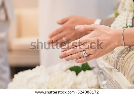 Hands pouring blessing water into bride's bands, Thai wedding