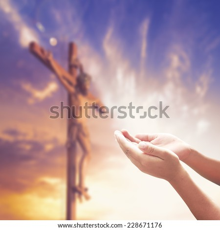 Hands praying over blurred Jesus on the cross over sunset - stock photo