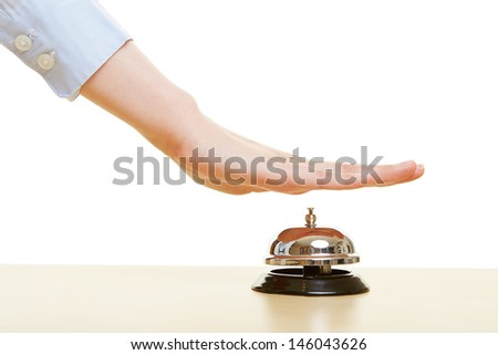 Hands pressing a hotel bell on a reception